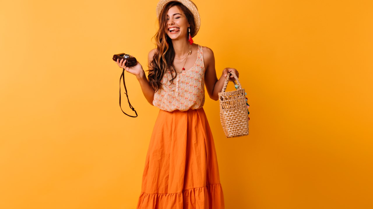 Blissful lady in trendy summer clothes posing with camera on yel