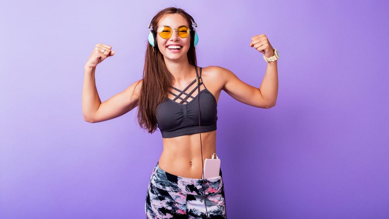 Exited sporty woman demonstrate muscule in studio.