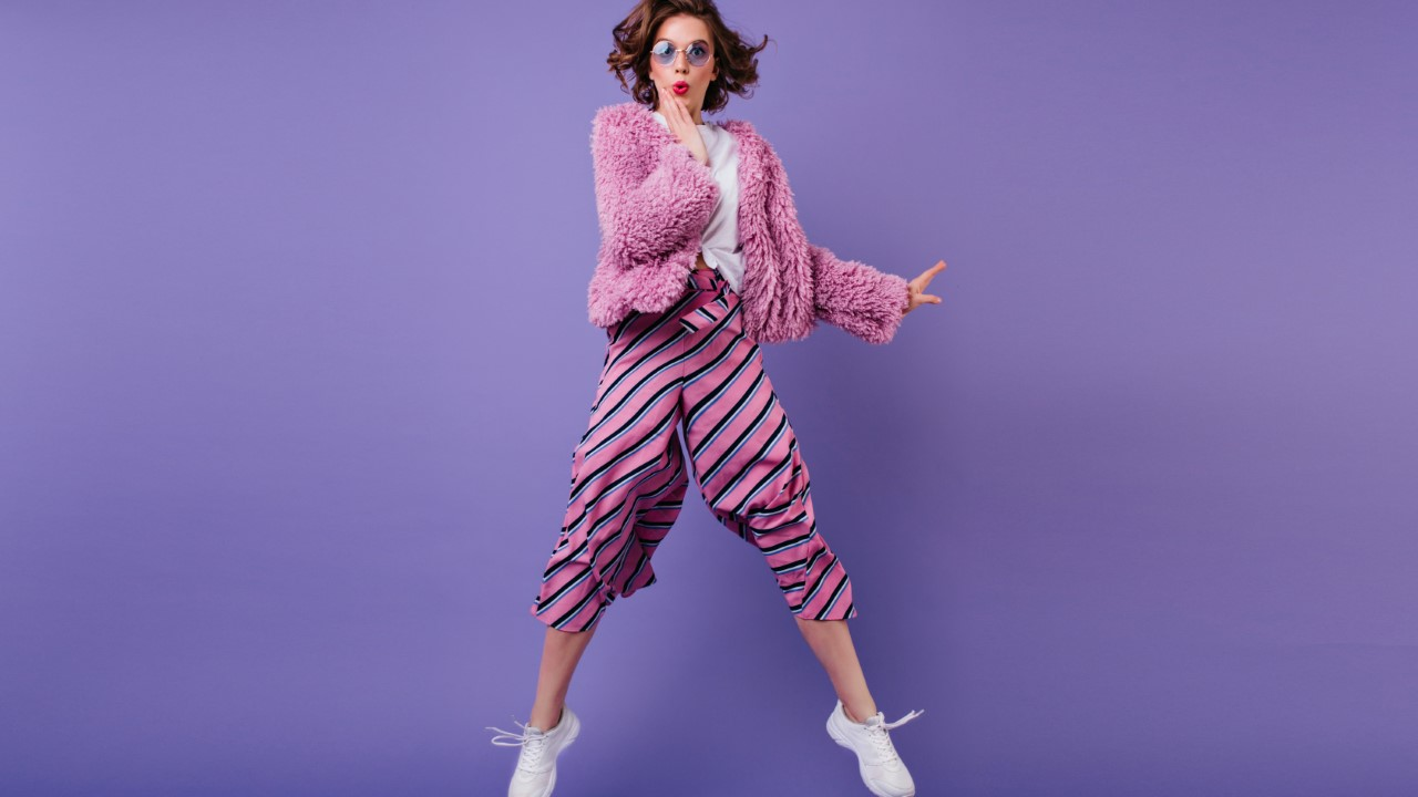 Full-length shot of glad curly woman in striped pants jumping on