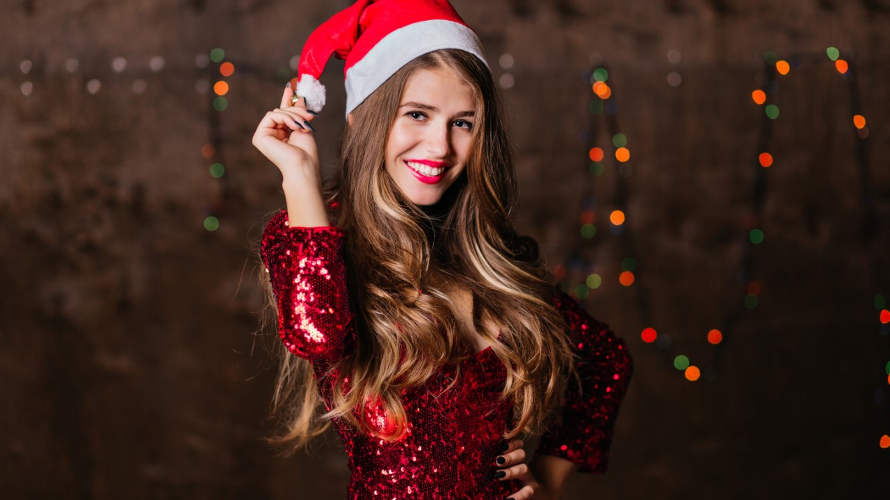 Long-haired woman in sparkle dress and santa claus hat expressing happiness. Appealing young lady having fun at new year party..