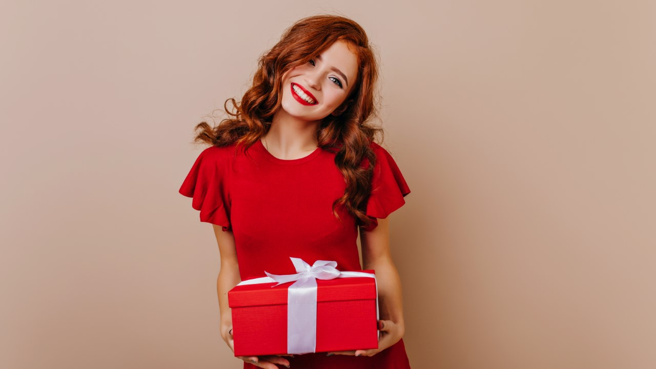 Red-haired birthday girl smiling to camera. Winsome female model