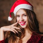 Sensual european woman in Santa Claus hat posing on dark background and smiling. Charming blonde girl in new year costume playfully touching her face with finger..