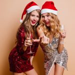 Stylish girls in santa claus hats celebrating new year together. Laughing ladies in party dresses drinking champagne in christmas..