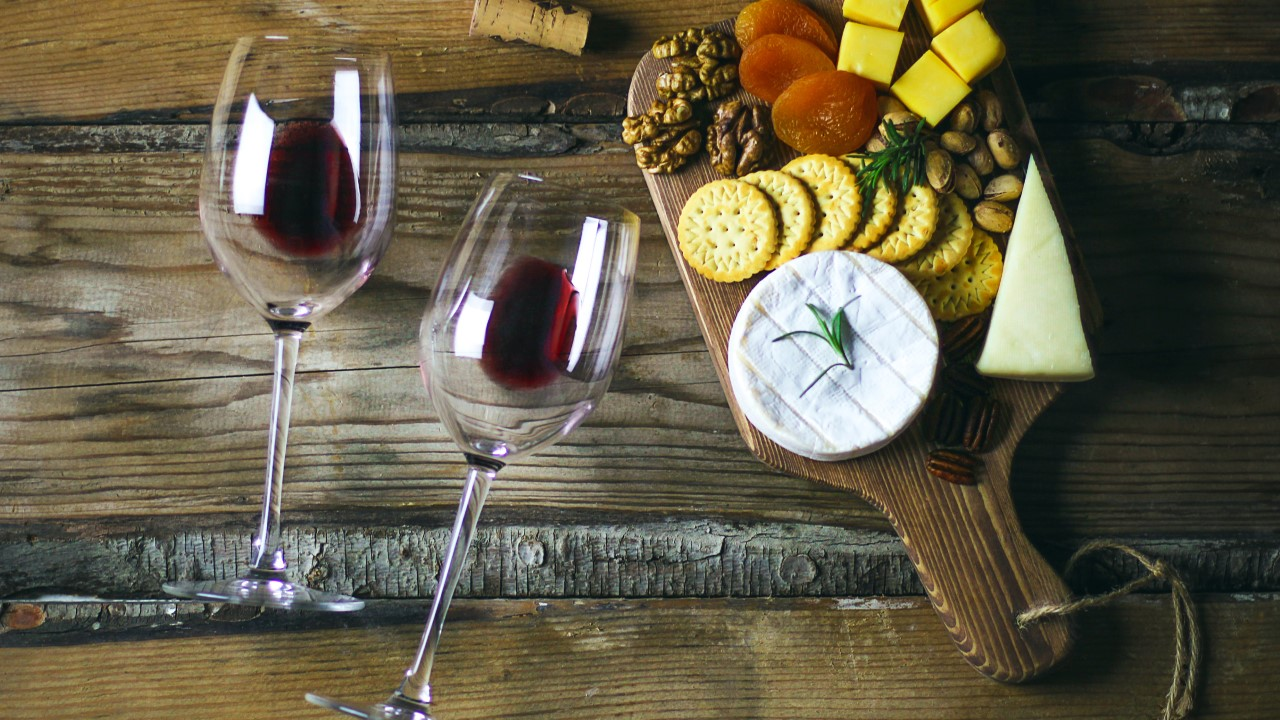 two red wine glass and cheese platter on rustic background top v