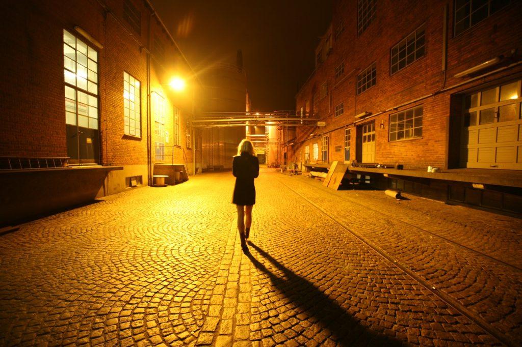 Woman Walking on Street at Night